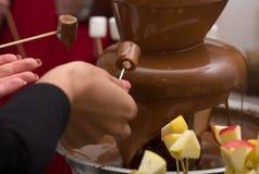 巧克力喷泉和对它伸出手 免版税库存图片