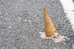 巧克力圆锥形的冰淇淋杯在水泥地板上滴下了 免版税库存照片