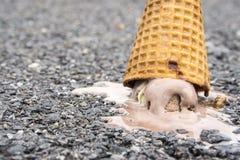 巧克力圆锥形的冰淇淋杯在水泥地板上滴下了 库存图片