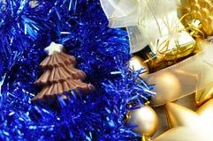 巧克力圣诞树形状显示与闪亮金属片和金黄圣诞节装饰 免版税图库摄影