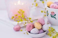 巧克力在淡色的复活节彩蛋在陶瓷匙子,灼烧的蜡烛,白色餐巾 免版税库存照片