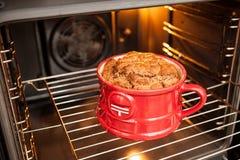 巧克力在烤箱烹调的一个红色杯子的焦糖蛋糕 库存照片