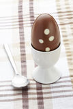 巧克力在蛋杯和匙子的复活节彩蛋 库存照片