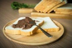 巧克力在面包片传播了在木板材的 集中于面包用巧克力传播对此 库存图片