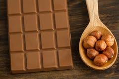 巧克力块和被剥皮的榛子在匙子 免版税库存照片