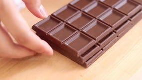 巧克力块在木背景的手上 免版税库存照片