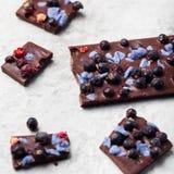 巧克力块用莓果和糖煮的紫罗兰色瓣 背景灰色石头 库存图片