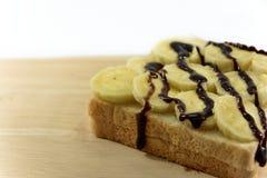 巧克力垂度是一新鲜的在bnanas和在木板安置的面包切片 免版税图库摄影