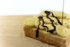 巧克力垂度是一新鲜的在bnanas和在木板安置的面包切片 图库摄影