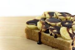 巧克力垂度是一新鲜的在bnanas和在木板安置的面包切片 库存图片