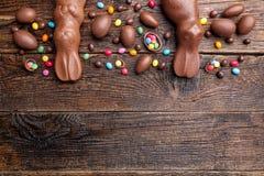 巧克力复活节兔子和鸡蛋在木背景 图库摄影