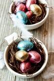 巧克力复活节彩蛋在五颜六色的封皮的 免版税库存图片