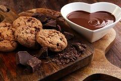 巧克力奶油熔化了和在木桌上的巧克力片 免版税库存照片