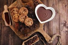 巧克力奶油熔化了和在木桌上的巧克力片 库存照片