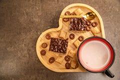 巧克力奶蛋烘饼和曲奇饼在一个木盘子以心脏的形式和一个杯子巧克力热饮 免版税图库摄影