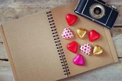 巧克力心脏的顶视图图象,葡萄酒照片照相机和打开在木桌上的空白的笔记本 库存图片