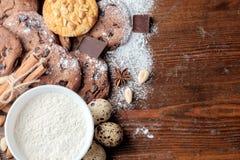 巧克力曲奇饼、曲奇饼用花生和疏散坚果在黑暗的土气纹理 免版税库存照片