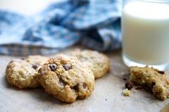 巧克力曲奇饼和牛奶木表面上 免版税图库摄影