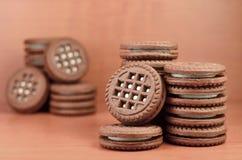 巧克力曲奇饼堆用木棕色表面上的香草白色奶油色谎言填装了 甜和鲜美三明治圆的biscu 免版税库存图片