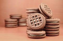 巧克力曲奇饼堆用木棕色表面上的香草白色奶油色谎言填装了 甜和鲜美三明治圆的biscu 免版税库存照片