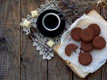巧克力曲奇饼的浪漫构成与白色奶油、咖啡和花束淡紫色的在木背景 有选择性的foc 免版税图库摄影