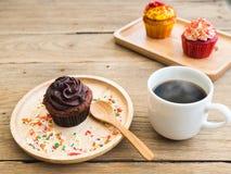 巧克力杯形蛋糕投入了一块球状木板材 在杯形蛋糕旁边有葡萄酒闹钟和加奶咖啡杯子 免版税库存照片