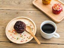 巧克力杯形蛋糕投入了一块球状木板材 在杯形蛋糕旁边有葡萄酒闹钟和加奶咖啡杯子 图库摄影