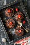 巧克力杯形蛋糕用在一个木箱的奶油色和新鲜的草莓 平的位置 库存图片
