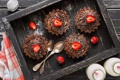 巧克力杯形蛋糕用在一个木箱的奶油色和新鲜的草莓 平的位置 图库摄影