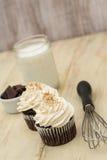 巧克力杯形蛋糕用牛奶和Wisk 库存图片