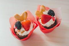 巧克力杯形蛋糕用草莓和黑莓莓果和曲奇饼甜假日点心的 库存照片