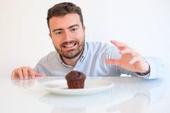 巧克力松饼诱惑的饮食的贪婪的人 库存照片