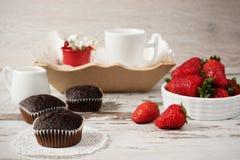 巧克力松饼,咖啡,草莓,一个花瓶白花 轻的木土气背景 免版税库存图片