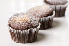 巧克力果仁巧克力杯子结块用搽粉的糖在白色大理石背景 免版税图库摄影