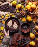 巧克力果仁巧克力用在烘烤盘的一个梨由在毛线衣的一只女性手举行 食物汇聚,样式 秋天 免版税库存图片