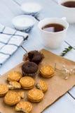 巧克力果仁巧克力和一杯茶在木桌上的 免版税库存图片