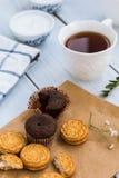 巧克力果仁巧克力和一杯茶在木桌上的 图库摄影