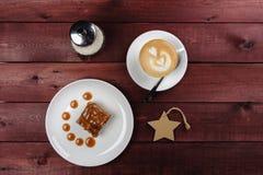 巧克力果仁巧克力片断和焦糖调味,一个杯子在一块白色板材的热奶咖啡 顶视图 库存照片