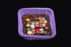 巧克力果仁糖和咖啡豆在淡紫色篮子 免版税库存图片