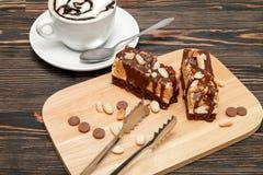 巧克力榛子蛋糕 与空气泡沫的热的咖啡 免版税库存图片