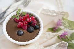 巧克力沫丝淋用在一把轻的餐巾的莓果和老匙子和叉子 图库摄影