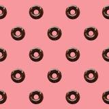 巧克力油炸圈饼的无缝的样式在粉红彩笔背景的 库存图片