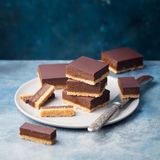 巧克力焦糖切片,酒吧,在板材的百万富翁脆饼 背景看板卡祝贺邀请 复制空间 免版税库存图片