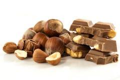 巧克力用在白色背景的榛子 免版税库存照片