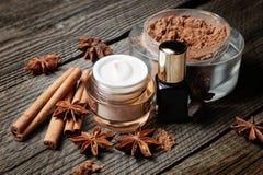 巧克力皮肤治疗 化妆瓶子用可可粉、化妆水和血清,肉桂条,茴香 免版税库存图片