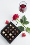 巧克力箱子、玫瑰和红葡萄酒玻璃在白色背景 库存照片