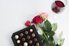 巧克力箱子、玫瑰和红葡萄酒玻璃在白色背景 图库摄影