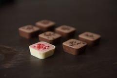 巧克力糖和一个草莓糖果在一张木桌上 免版税库存图片