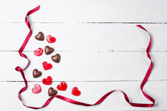 巧克力糖和红色棒棒糖与红色缎丝带 免版税图库摄影