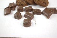 巧克力糖用在白色木头的巧克力饼干 免版税库存照片